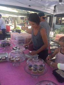 Tara with fox and fawn bakehouse displaying her cupcakes.
